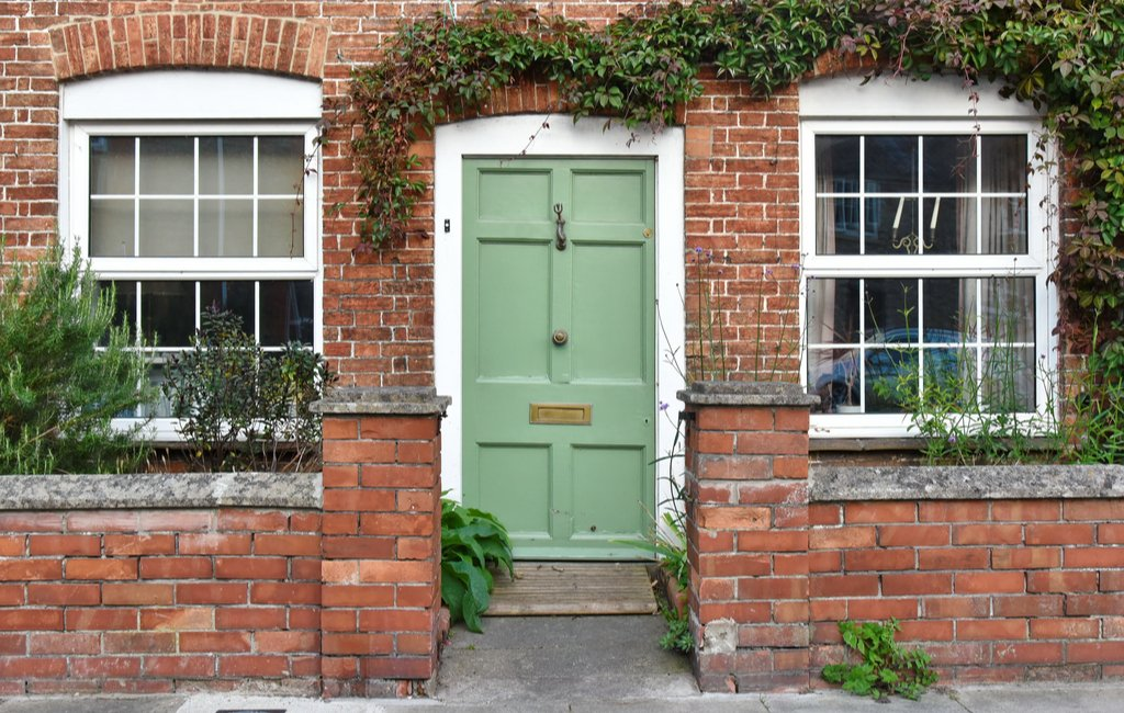Green front door to home surrounded by plants